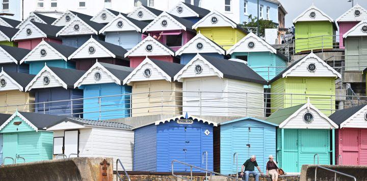 La gente se sienta en un muro a lo largo del paseo marítimo frente a las cabañas de playa en Walton-on-the-Naze, en el sureste de Inglaterra.
