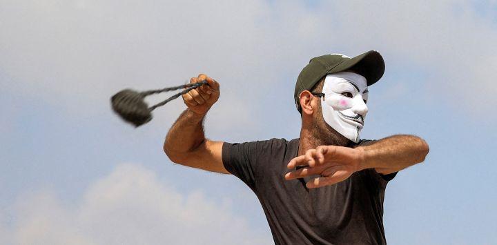 Un manifestante palestino lanza piedras a las fuerzas israelíes durante los enfrentamientos en la localidad de Beita, cerca de la ciudad ocupada de Naplusa, tras una protesta contra el puesto de avanzada israelí de Eviatar.