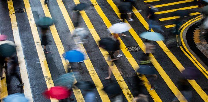 Peatones con paraguas cruzan una carretera en Hong Kong, mientras los patrones climáticos del tifón Cempaka traen fuertes lluvias a la ciudad.