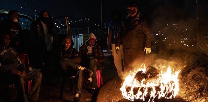 Miembros del Foro de Policía Comunitaria de Phoenix, un grupo de movilización de base en el que participan residentes locales, sentados alrededor de un neumático incendiado durante una vigilancia en Durban.