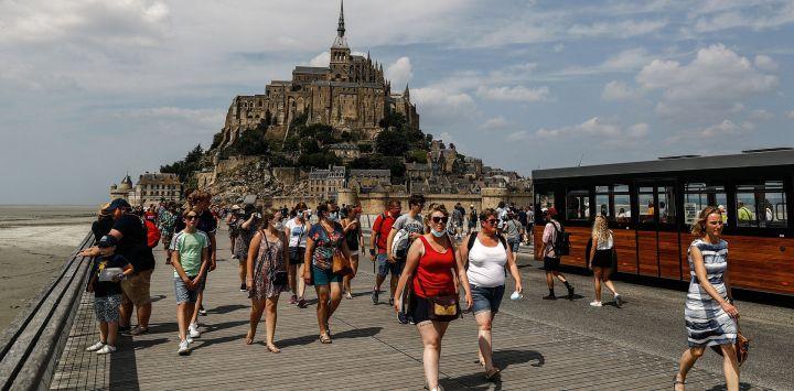 Turistas caminan frente al Mont-Saint-Michel, en Normandía, noroeste de Francia.