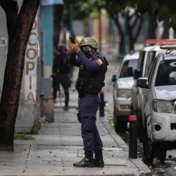 In this file photo taken on July 09, 2021, a member of the Bolivarían Police aims at a possible target after clashes with alleged members of a criminal gang at the Cota 905 barrio, in Caracas on July 9, 2021.