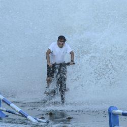 Esta foto muestra a un hombre andando en bicicleta mientras las olas, causadas por el tifón In-Fa, sobrepasan una barrera a lo largo de la costa marítima en Qingdao, en la provincia oriental china de Shandong. | Foto:STR / AFP