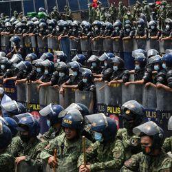 Policías antidisturbios se colocan en formación para bloquear a los manifestantes (no se ven la foto) que intentan marchar por una autopista en su camino hacia el Congreso para coincidir con el discurso anual del presidente sobre el estado de la nación, en los suburbios de Manila. | Foto:Ted Aljibe / AFP