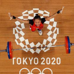 Esta imagen tomada con una cámara robótica muestra a la indonesia Windy Cantika Aisah reaccionando mientras compite en la competición de halterofilia femenina de 49 kg durante los Juegos Olímpicos de Tokio 2020 en el Foro Internacional de Tokio. | Foto:Chris Graythen / POOL / AFP