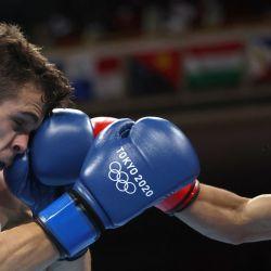 El argentino Ramón Nicanor Quiroga (de rojo) y el español Gabriel Escobar Mascunano luchan durante su combate de boxeo de las preliminares masculinas mosca (48-52kg) durante los Juegos Olímpicos de Tokio 2020 en el Kokugikan Arena en Tokio. | Foto:Buda Mendes / POOL / AFP