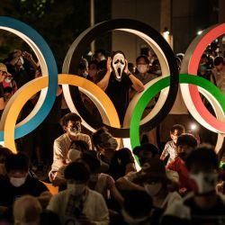 La gente espera cerca de la estatua de los Anillos Olímpicos cerca del Estadio Olímpico en Tokio. | Foto:Yasuyoshi Chiba / AFP