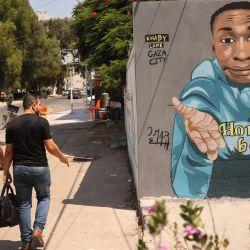 Unos palestinos pasan por delante de un arte mural que representa a Khabane    Foto:Mohammed Abed / AFP