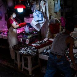Una mujer pesa marisco para un cliente en un puesto en el distrito de Wanchai de Hong Kong. | Foto:Isaac Lawrence / AFP