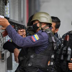In this file photo taken on July 09, 2021, members of the Bolívarian National Police aim at possibe targets after clashes with alleged members of a criminal gang at the Cota 905 neighbourhood in Caracas on July 9, 2021.
