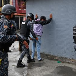 In this file photo taken on July 09, 2021, members of the Bolívarian National Police frisk people during clashes with alleged members of a criminal gang in the surroundings of La Cota 905 barrio in Caracas, on July 9, 2021.