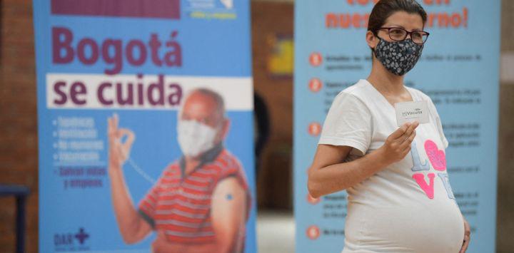 Una mujer embarazada muestra la tarjeta de vacunación después de recibir una dosis de la vacuna Pfizer-BioNTech contra el COVID-19 en un centro de vacunación en Bogotá.
