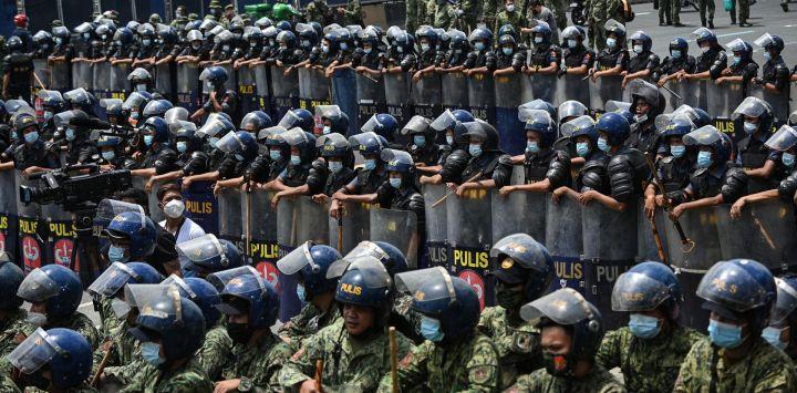 Policías antidisturbios se colocan en formación para bloquear a los manifestantes (no se ven la foto) que intentan marchar por una autopista en su camino hacia el Congreso para coincidir con el discurso anual del presidente sobre el estado de la nación, en los suburbios de Manila.