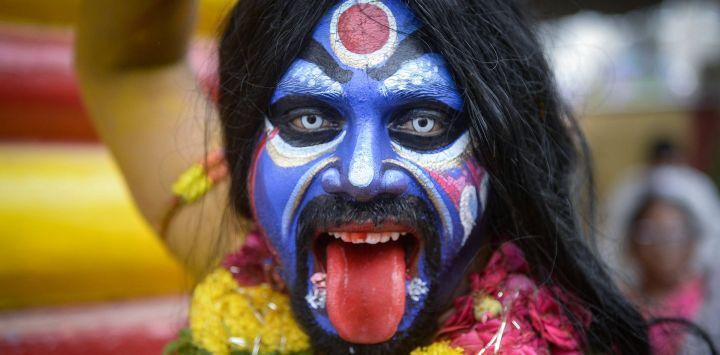 Artistas vestidos como dioses hindúes reaccionan ante la cámara durante la procesión del festival Bonalu en Secunderabad, la ciudad gemela de Hyderabad.