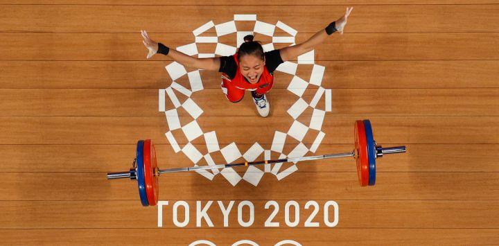 Esta imagen tomada con una cámara robótica muestra a la indonesia Windy Cantika Aisah reaccionando mientras compite en la competición de halterofilia femenina de 49 kg durante los Juegos Olímpicos de Tokio 2020 en el Foro Internacional de Tokio.