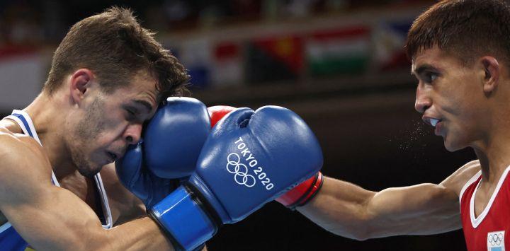 El argentino Ramón Nicanor Quiroga (de rojo) y el español Gabriel Escobar Mascunano luchan durante su combate de boxeo de las preliminares masculinas mosca (48-52kg) durante los Juegos Olímpicos de Tokio 2020 en el Kokugikan Arena en Tokio.