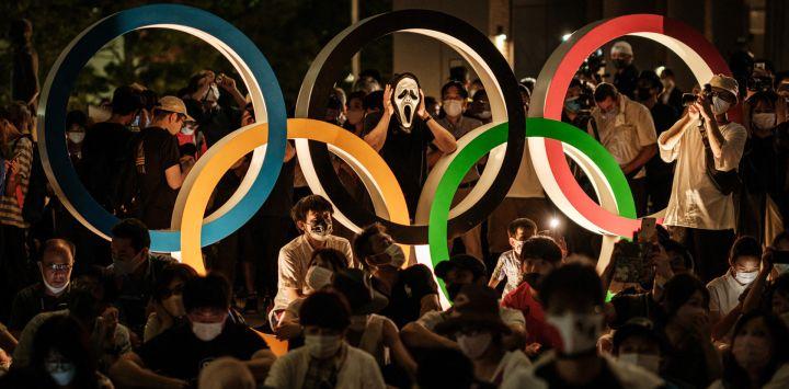 La gente espera cerca de la estatua de los Anillos Olímpicos cerca del Estadio Olímpico en Tokio.