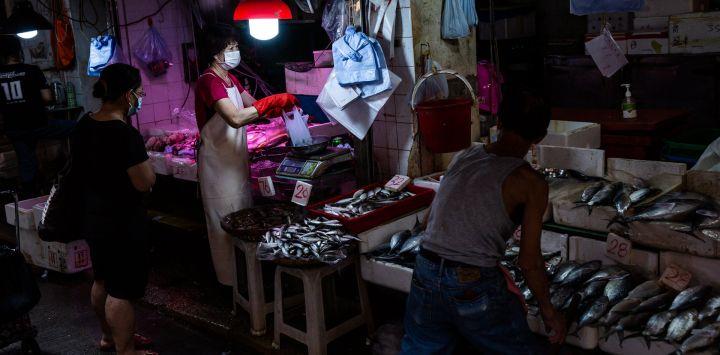 Una mujer pesa marisco para un cliente en un puesto en el distrito de Wanchai de Hong Kong.