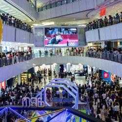 La gente en un centro comercial observa y anima a Doo Hoi-kem en Hong Kong, mientras juega en un partido de tenis de mesa individual femenino en los Juegos Olímpicos de Tokio.   Foto:Isaac Lawrence / AFP