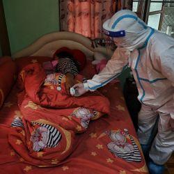 Una voluntaria de la organización Zendai comprueba los niveles de oxígeno en sangre de una mujer en aislamiento domiciliario en una comunidad afectada por Covid-19 en el distrito de Nong Chok, en las afueras de Bangkok, mientras las camas de hospital para los pacientes infectados siguen escaseando en todo el país.   Foto:Lillian Suwanrumpha / AFP