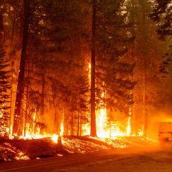 Un camión de Cal Fire circula cerca de las llamas durante el incendio Dixie en la comunidad de Prattville del condado de Plumas.   Foto:Josh Edelson / AFP