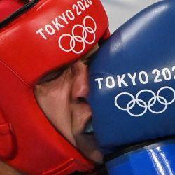 La rumana Maria Claudia Nechita recibe un golpe de la japonesa Sena Irie durante su combate de boxeo en categoría pluma femenina (54-57 kg) de cuartos de final durante los Juegos Olímpicos de Tokio 2020 en el Kokugikan Arena en Tokio.   Foto:Luis Robayo / AFP