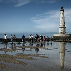 Turistas caminan frente al faro de Cordouan durante la marea baja en la costa de Le Verdon-sur-Mer, en el suroeste de Francia.   Foto:Philippe Lopez / AFP