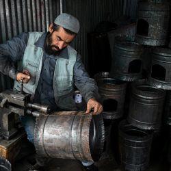 Un trabajador fabrica calentadores tradicionales en un taller de Kabul. | Foto:Sajjad Hussain / AFP