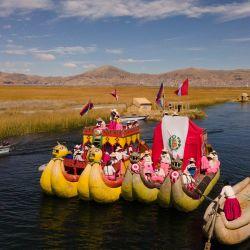 Artesanos de la asociación Qota Tika marchan en botes con la bandera peruana durante una celebración en conmemoración del bicentenario del Día de la Independencia de Perú, cerca del lago Titicaca en Puno, Perú. | Foto:Carlos Mamani / AFP