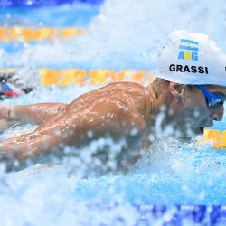 El argentino Santiago Grassi compite en una eliminatoria de la prueba masculina de 100 metros mariposa durante los Juegos Olímpicos de Tokio 2020 en el Centro Acuático de Tokio. | Foto:Attila Kisbenedek / AFP