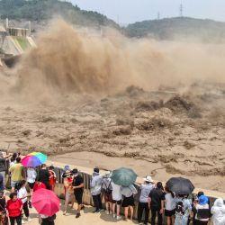 Esta foto aérea muestra a la gente viendo cómo se libera el agua de la presa del embalse de Xiaolangdi en Luoyang, en la provincia central china de Henan. | Foto:STR / AFP