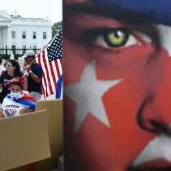 La gente se reúne para una protesta contra Cuba mientras agitan carteles y banderas cubanas en la Plaza Lafayette cerca de la Casa Blanca en Washington DC. | Foto:Brendan Smialowski / AFP