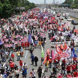 Manifestantes marchan por una autopista en su camino hacia el Congreso para coincidir con el discurso anual del presidente sobre el estado de la nación que se espera más tarde en el día, en los suburbios de Manila. | Foto:Ted Aljibe / AFP
