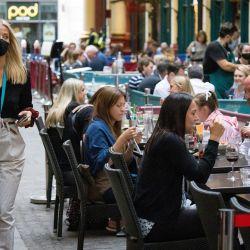 Una mujer con una mascarilla pasa por delante de tiendas y restaurantes en el mercado de Leadenhall, en la City de Londres. | Foto:Tolga Akmen / AFP