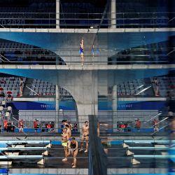 Los clavadistas se ven en el reflejo de una ventana mientras calientan antes de la prueba final de clavados de plataforma de 10 metros sincronizados femeninos durante los Juegos Olímpicos de Tokio 2020 en el Centro Acuático de Tokio. | Foto:Odd Andersen / AFP
