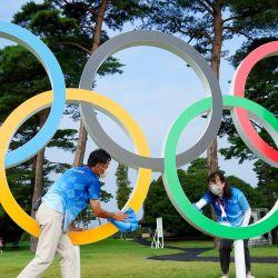 Los voluntarios limpian las gotas de lluvia en el símbolo olímpico antes de comenzar la primera ronda del juego individual de golf durante los Juegos Olímpicos de Tokio 2020 en el Kasumigaseki Country Club en Kawagoe. | Foto:Yoshihiro Iwamo / AFP