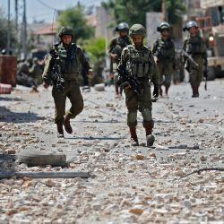 Soldados y guardias fronterizos israelíes caminan por una calle llena de piedras durante los enfrentamientos con manifestantes palestinos en la ciudad de Beit Ummar, al noroeste de la ciudad de Hebrón. | Foto:Ahmad GharabliH / AFP