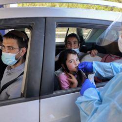 Un médico realiza una prueba de hisopo de coronavirus COVID-19 en un niño en un vehículo en un complejo de pruebas de coronavirus del comando Home Front en Jerusalén. | Foto:Menahem Kahana / AFP