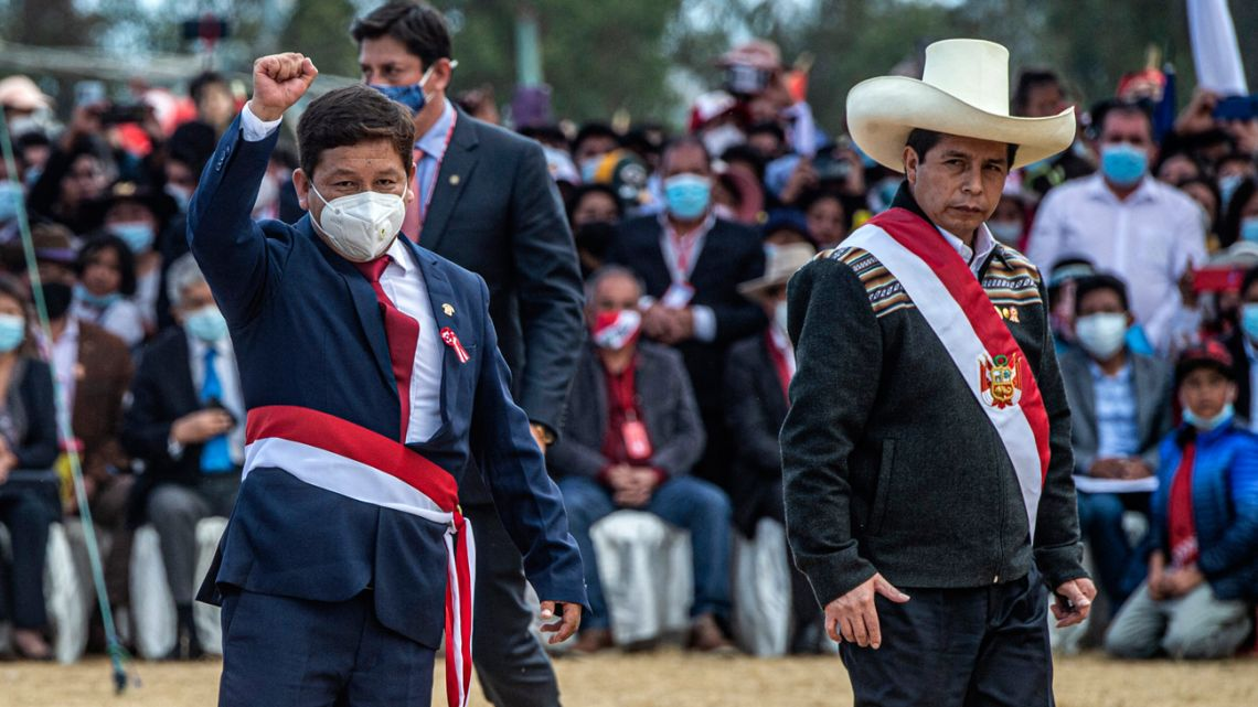 Guido Bellido (left) raises his fist next to Peru's President Pedro Castillo (right) at Pampa de la Quinua in Ayacucho, southern Peru, on July 29, 2021, after being sworn-in as prime minister.