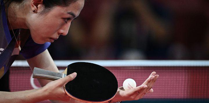 La singapurense Yu MengYu sirve a la japonesa Mima Ito durante el partido de tenis de mesa individual femenino por la medalla de bronce en el Gimnasio Metropolitano de Tokio durante los Juegos Olímpicos de Tokio 2020 en Tokio.