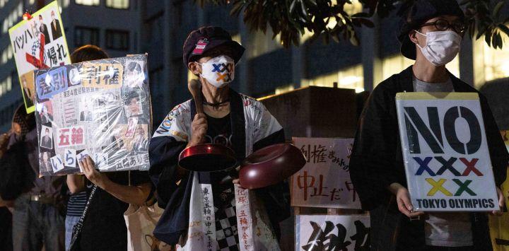 Activistas sostienen pancartas mientras se reúnen para una manifestación de protesta contra los Juegos Olímpicos de Tokio 2020 frente a la oficina del Primer Ministro, en Tokio.