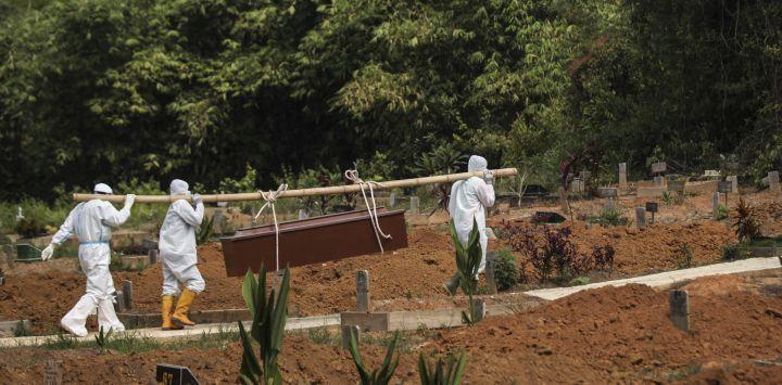 Sepultureros llevan el ataúd de una víctima de Covid-19 coronaivurs para su entierro en un cementerio en Palembang.