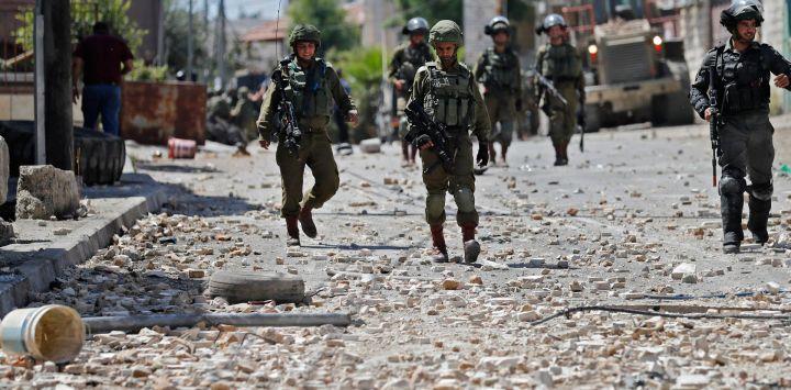 Soldados y guardias fronterizos israelíes caminan por una calle llena de piedras durante los enfrentamientos con manifestantes palestinos en la ciudad de Beit Ummar, al noroeste de la ciudad de Hebrón.