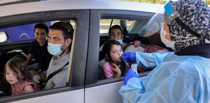 Un médico realiza una prueba de hisopo de coronavirus COVID-19 en un niño en un vehículo en un complejo de pruebas de coronavirus del comando Home Front en Jerusalén.