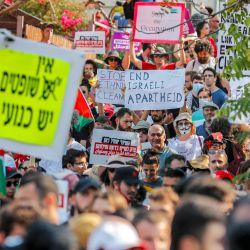 Activistas palestinos, israelíes y extranjeros levantan pancartas y carteles durante una manifestación contra la ocupación israelí y la actividad de los asentamientos en los territorios palestinos y en el este de Jerusalén, en el barrio palestino de Sheikh Jarrah. | Foto:Ahmad Gharabli / AFP