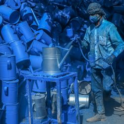 Un trabajador pinta con spray latas en un taller en Kabul. | Foto:Sajjad Hussain / AFP