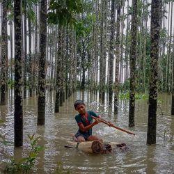 Un niño vadea una zona inundada utilizando una balsa improvisada en Maulovir Para, Cox's Bazar, después de que las inundaciones monzónicas y los corrimientos de tierra hayan dejado incomunicadas a más de 300.000 personas en pueblos del sureste de Bangladés y hayan causado la muerte de al menos 20 personas. | Foto:Tanbir Miraj / AFP