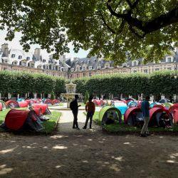 Manifestantes alrededor de tiendas de campaña durante una manifestación convocada por la asociación Utopía para pedir viviendas para migrantes y personas sin hogar, en la Plaza de los Vosgos de París. | Foto:Alain Jocard / AFP