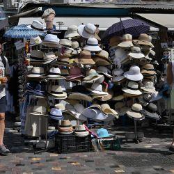 Personas pasan por delante de una tienda de sombreros en la céntrica plaza de Monastiraki de Atenas durante una ola de calor. | Foto:Louisa Gouliamaki / AFP