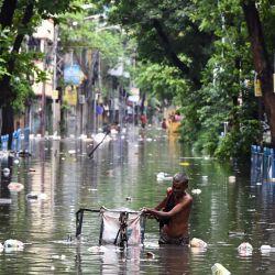 Un hombre empuja su triciclo a través de las aguas de la inundación tras las lluvias en Calcuta. | Foto:Dibyangshu Sarkar / AFP